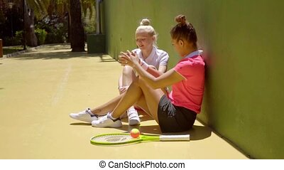 Two trendy sporty young women friends sitting in the sun...