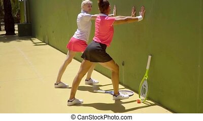 Two sporty young woman doing warming up exercises