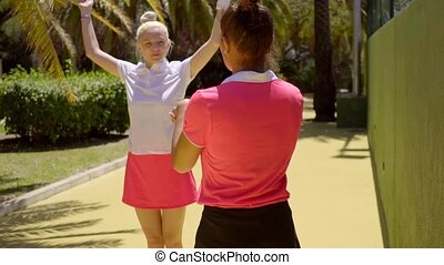 Two sporty young tennis players warming up - Two sporty...