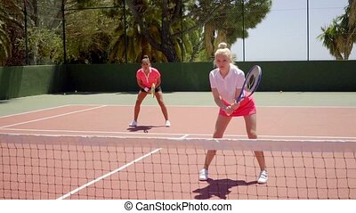 Two pretty women playing a game of tennis doubles - Two...