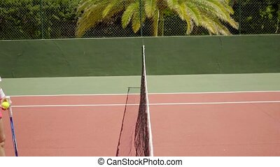 Two female tennis opponents shaking hands over the net at...