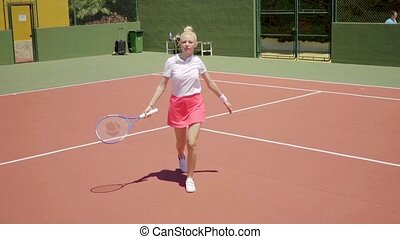 Angry young woman tennis player yelling on court