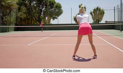 Woman tennis player waiting to receive service - Rear view...