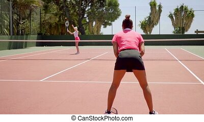 Trendy young tennis players training on a court - Two trendy...