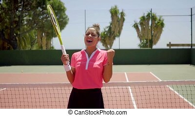 Attractive young tennis player cheering and punching the air...