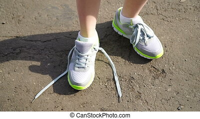 girl stopped running to tie the laces on running shoes...