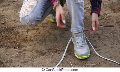 young girl commits an outdoor walk and stopped to tie his...