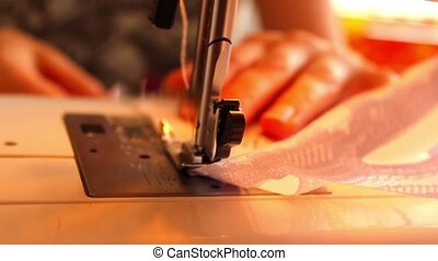 The woman begins to sew on the sewing machine - The woman...