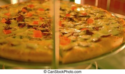 Pizza on rotating display closeup view, warm color,...