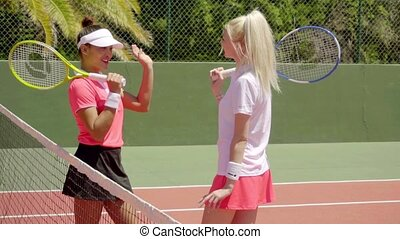 Pair of friends talking on tennis court - Pair of attractive...