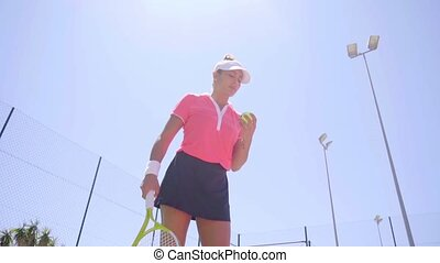 Low angle view on woman bouncing tennis ball in preparation...