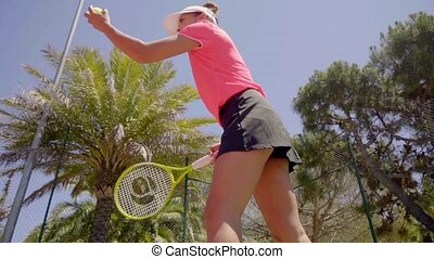 Pretty young woman serving the ball in tennis - Low angle...