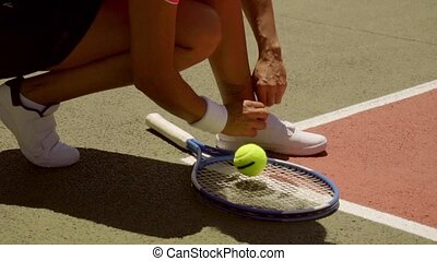 Female tennis player tying her laces on her sports shoes...