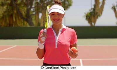 Smiling gorgeous young female tennis player standing holding...
