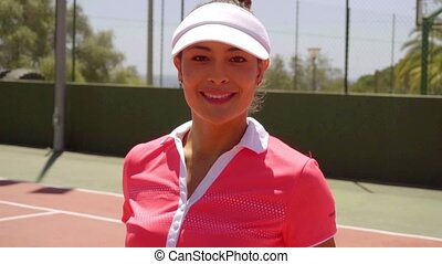 Thoughtful attractive young female tennis player standing on...
