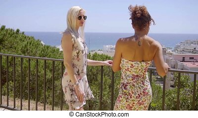 Two young women chatting on a balcony - Two attractive...