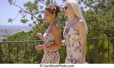 Two young girlfriends walking on a patio arm in arm smiling...