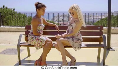 Two trendy young women sitting chatting