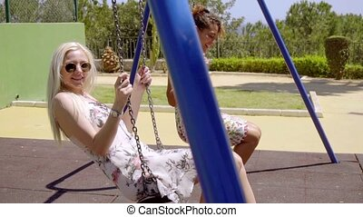 Pretty blond woman relaxing on a swing