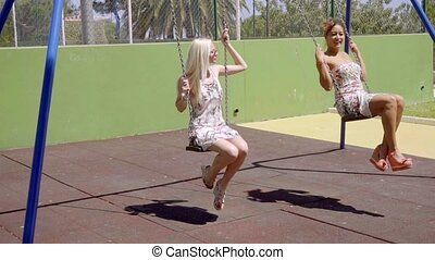 Two attractive women swinging in a park
