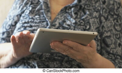 Old woman holding a digital tablet sitting on sofa