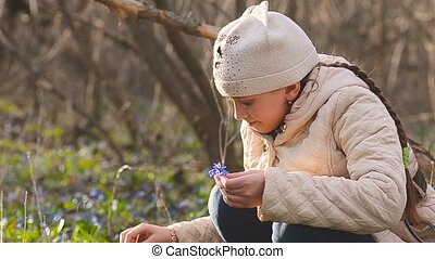 Girl collects blue snowdrops in the forest - Beautiful girl...