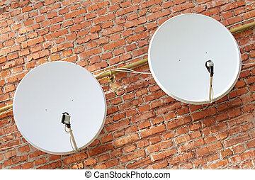 Two satellite dishes on the brick wall