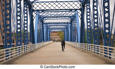 Cyclist Riding Across Blue Bridge Grand Rapids Michigan...