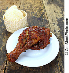 Roasted chicken drumstick on white plate