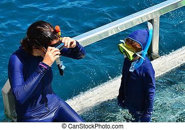 Mother and daughter prepare to snorkeling dive - Mother and...