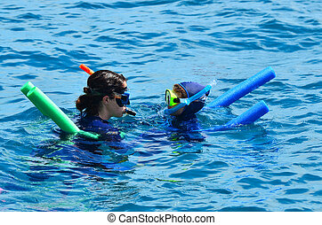 Woman instructor teach little girl how to snorkelling dive
