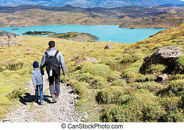 family hiking in patagonia - backview of young father and...
