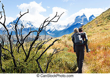 family hiking in patagonia - young father giving his son a...
