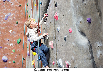 kid rock climbing - determined little boy enjoying rock...