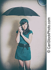 Young woman in 70s style portrait with umbrella in studio -...
