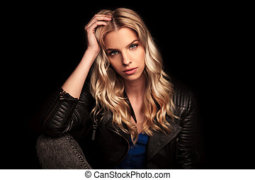 young woman in leather jacket resting her head on palm -...