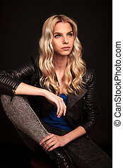 side view of a blond woman in leather jacket sitting