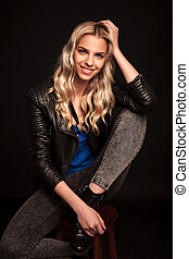 blond woman in leather jacket resting her head on hand -...