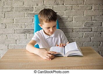 6 year old boy in a white polo shirt reading a book at the...