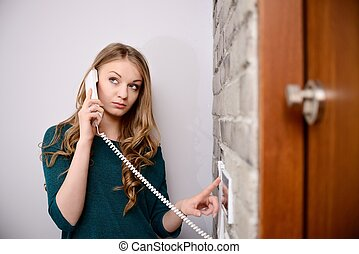 Young blonde woman talking on the intercom and presses the...