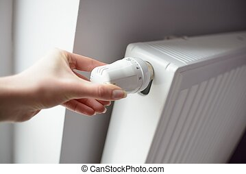 Closeup on woman hand adjusting temperature by thermostat