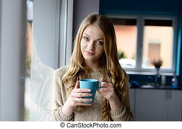 blonde woman drinking coffee from a cup - A beautiful young...