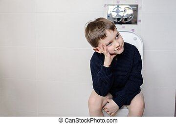 Thinking 6 year old boy sitting on the toilet. Dressed in a...