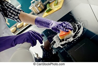 female hands washes the induction hob. Purple protective...