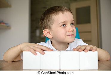 Child plays with white cubes.