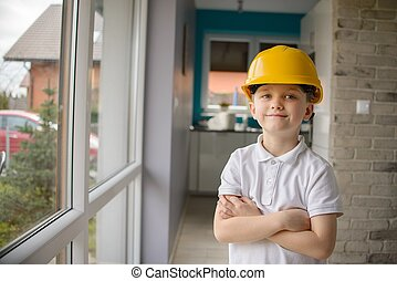 Little 6 year old boy posing by a window with a yellow...