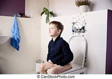 Happy smiling 6 year old boy sitting on the toilet. Dressed...