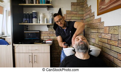 eccentric stylist washes head respectable men. Businessman...