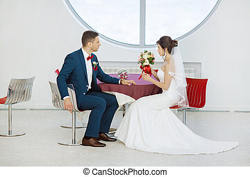 Bride and groom sitting in indoors cafe