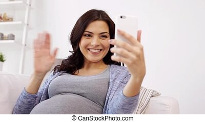 pregnant woman in smartphone video chat at home - pregnancy,...